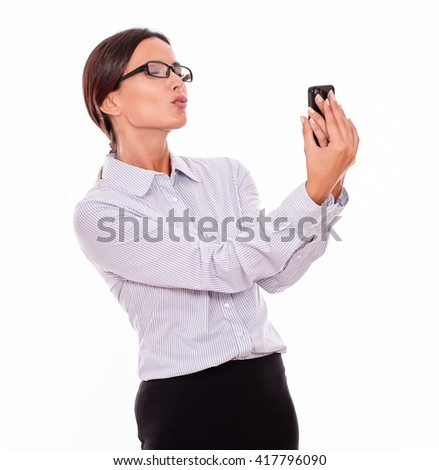 Happy businesswoman taking selfies with her cell phone and blowing a kiss in a satisfied gesture while wearing her straight hair back and a button down shirt on a white background - stock photo