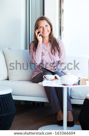 Happy businesswoman talking on the cellphone and writing in organizer in a coffee house