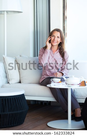 Happy businesswoman talking on the phone and writing in organizer in a coffee shop