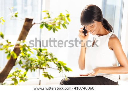 Happy businesswoman talking on the phone in office - stock photo
