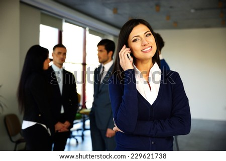 Happy businesswoman talking on the phone with colleagues on background - stock photo