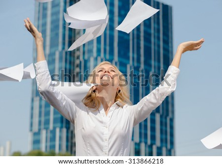 Happy businesswoman throwing away all the documents outdoors. Beautiful lady in white blouse raised her hands to the sky. - stock photo