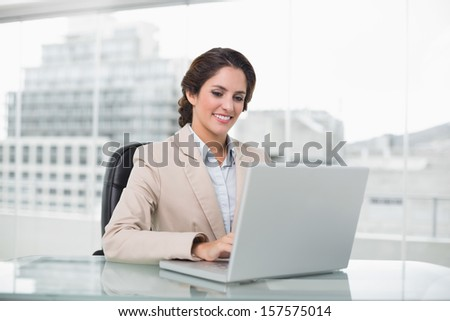 Happy businesswoman typing on laptop at her desk in bright office