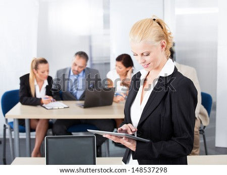 Happy Businesswoman Using Digital Tablet In Front Of Colleagues - stock photo