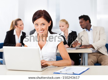 Happy Businesswoman Using Laptop In Front Of Colleagues
