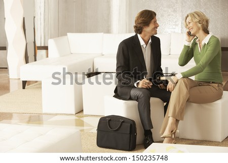 Happy businesswoman using mobile phone while looking at businessman in office lobby - stock photo
