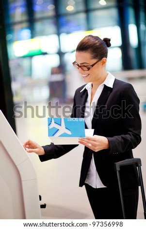 happy businesswoman using self help check in machine at airport - stock photo