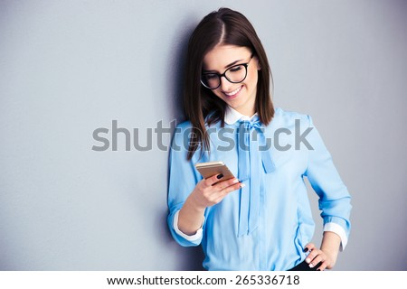 Happy businesswoman using smartphone over gray background. Wearing in blue shirt and glasses.  - stock photo