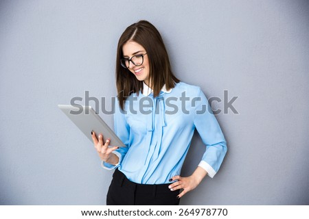Happy businesswoman using tablet computer over gray background. Wearing in blue shirt and glasses - stock photo