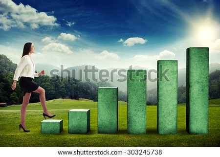 happy businesswoman walking up to the top of concrete diagram over beautiful landscape with forest, hills and sky - stock photo