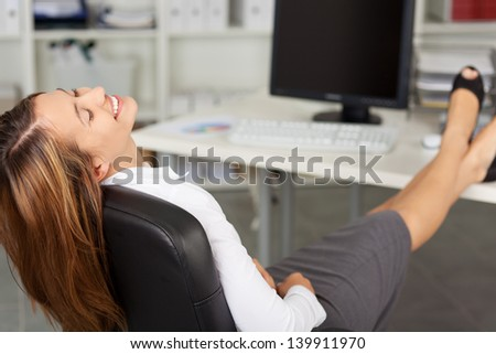 Happy businesswoman with eyes closed relaxing on office chair - stock photo