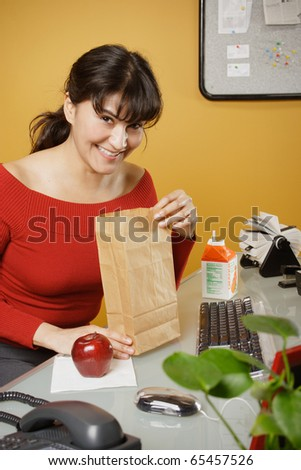 Happy businesswoman with lunch bag - stock photo