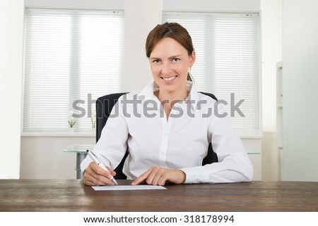 Happy Businesswoman With Pen Signing Cheque At Desk - stock photo