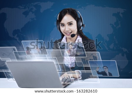 Happy businesswoman with pictures interface in front of laptop on world map background - stock photo