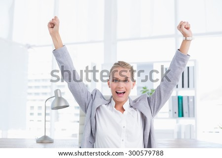 Happy businesswoman with raised arms in her office