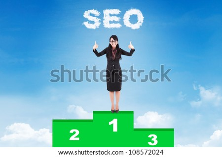 Happy businesswoman with SEO strategy standing on podium - stock photo
