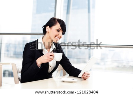 Happy businesswoman with tablet drinking coffee