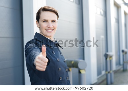 Happy businesswoman with thumbs up on front of warehouse - stock photo