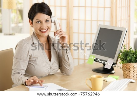 Happy businesswoman working at desk in office, talking on phone, using calculator. Copyspace on screen. - stock photo