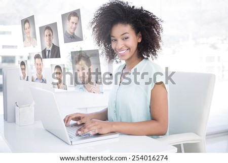 Happy businesswoman working on her laptop against profile pictures - stock photo