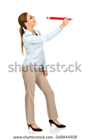 Happy businesswoman writing with big pencil. - stock photo