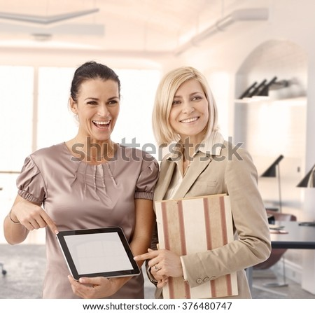 Happy businesswomen at office showing tablet, blank screen