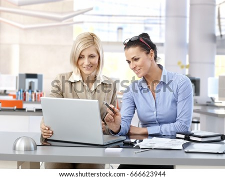Happy businesswomen sitting at desk working together with laptop in modern office.