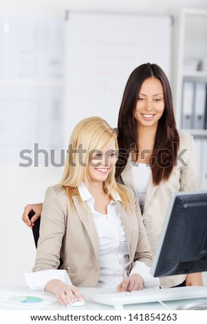 Happy businesswomen using computer together at desk in office
