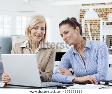Happy businesswomen working together, using laptop, smiling.