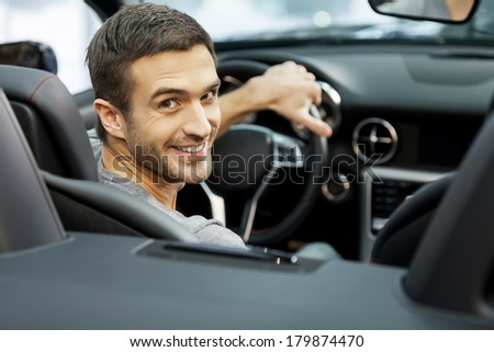 Happy cabriolet owner at the dealership. Handsome young men sitting at front seat of the car looking at camera - stock photo