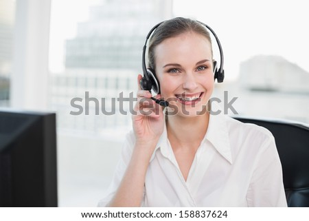 Happy call center agent looking at camera in her office