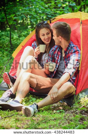 Happy camping couple in tent drinking coffee. Camping, hiking, forest.