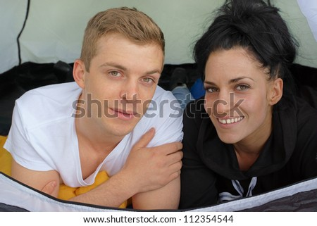 Happy camping couple smiling in a tent - stock photo
