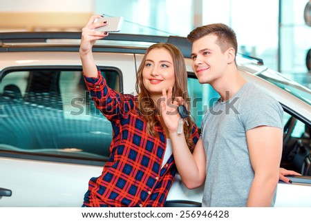 Happy car owners. Young couple standing near the car at the dealership and holding a key while making a selfie - stock photo