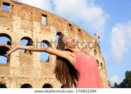 Happy carefree elated travel woman by Colosseum, Rome, Italy with arms raised out and up in ecstatic happiness expression. Travel concept with beautiful mixed race Asian woman in front of Coliseum. - stock photo