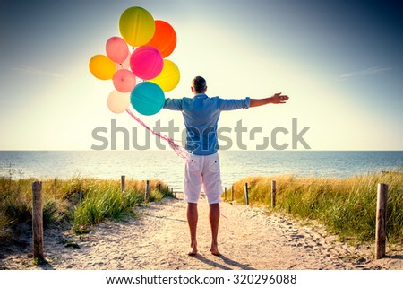 happy carefree male looking horizon ocean from dune - stock photo
