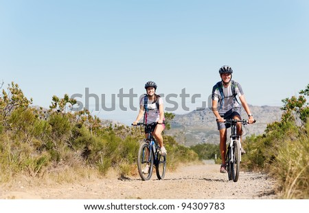 Happy carefree mountain bike couple cycling outdoors and leading a healthy lifestyle. - stock photo