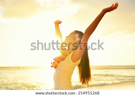 Happy carefree woman free in Hawaii beach sunset. Beautiful woman in the golden sunshine glow of sunset with arms outspread and face raised in sky enjoying peace, serenity in nature. - stock photo