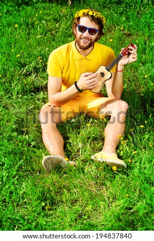 Happy carefree young man sitting on a grass and playing his little guitar. Summer, freedom, hippie. - stock photo