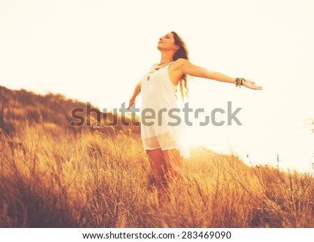 Happy Carefree Young Woman Outdoors. Fashion Lifestyle Portrait. Soft warm sunny colors.  - stock photo