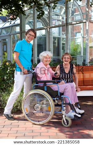 Happy Caregivers and Elderly Captured Outside Artistic Glassy Building Surrounded by Green Plants. - stock photo