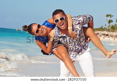 Happy Caribbean vacation couple relaxing together enjoying their holidays in perfect getaway in sunny tropical destination. Couple in love, summer luxury vacation in Dominican Republic.