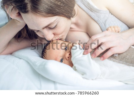 Happy caring mother holding baby boy in the bedroom. The concept of the tenderness of motherhood and family values