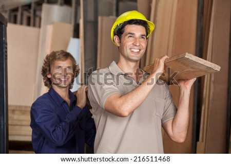 Happy carpenters carrying wooden plank on shoulders while looking away in workshop - stock photo