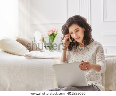 Happy casual beautiful woman working on a laptop in the house. - stock photo