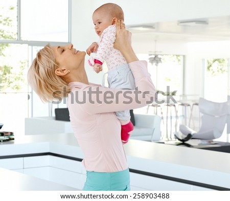 Happy casual blonde caucasian mother with cute baby at bright home indoors. Holding, raising, joy, family, smiling, standing. - stock photo