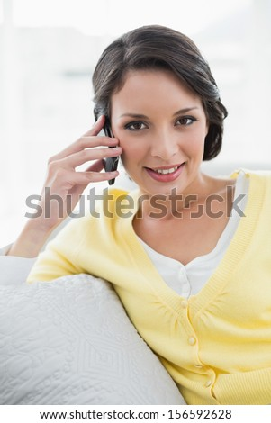 Happy casual brunette in yellow cardigan calling with her mobile phone sitting on a couch in bright living room - stock photo