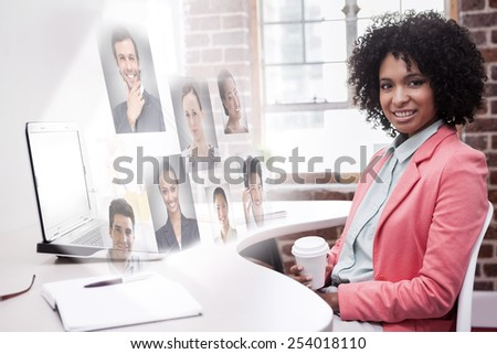 Happy casual businesswoman sitting at desk against profile pictures - stock photo
