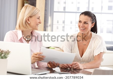 Happy casual businesswomen at office working in front of laptop computer checking business report papers, smiling. - stock photo