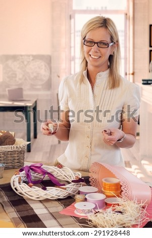 Happy casual caucasian blonde mid adult woman making valentine day wreath at home. Smiling, wearing glasses, looking at camera, standing at table, do it yourself, gift, present. - stock photo
